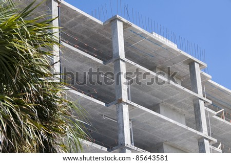 Multi-level commercial high-rise building construction with  blue sky and palm tree - stock photo