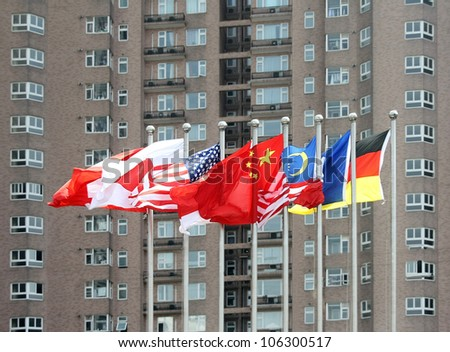 Multi-national flags in front of a high building - stock photo