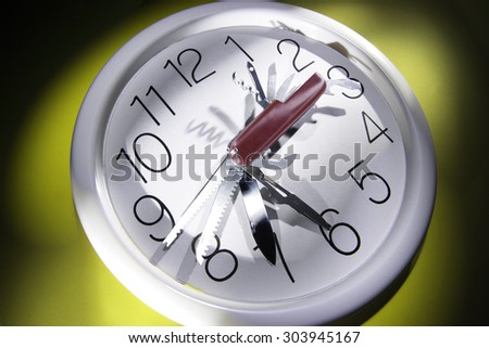 Multi-Purpose Tool on Wall Clock - stock photo