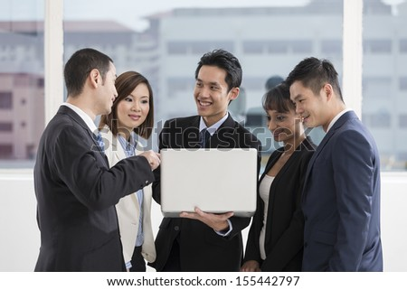 Multi-race business team working together around a laptop computer - stock photo