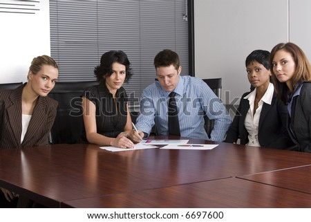 Multi-racial business team sitting around an office boardroom - stock photo