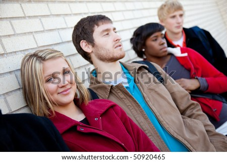 Multi-racial college students/friends outside against a brick wall - stock photo