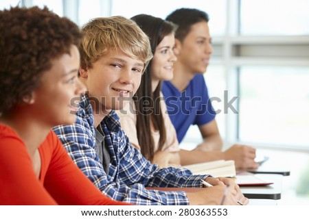 Multi racial teenage pupils in class, one smiling to camera - stock photo