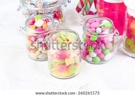 Multicolor candies in glass jars on color wooden background - stock photo