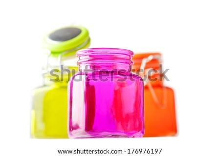 Multicolor glass jars on white - stock photo