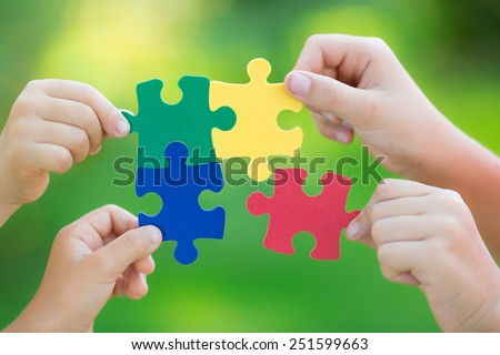 Multicolor puzzles in hands against green spring blurred background. Teamwork and solution concept - stock photo