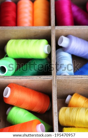 Multicolor sewing thread in wooden box, close-up - stock photo