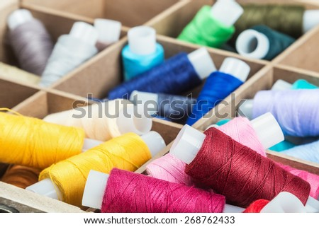 Multicolor sewing threads on wooden background. focus on the red thread - stock photo