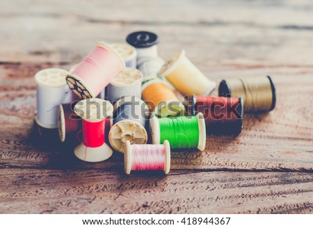 Multicolor sewing threads on wooden background.vintage tone - stock photo