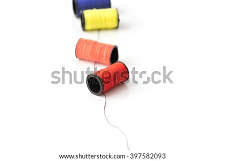 multicolor threads laying on black thread on white background best for sewing idea - stock photo
