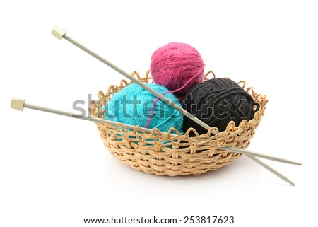 Multicolored balls and needles in basket isolated on white - stock photo