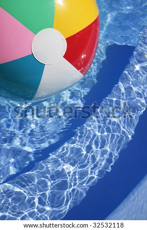 Multicolored Beachball in a beautiful blue swimming pool - stock photo