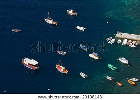 Multicolored boats in sunny harbor, view from above, Santorini, Greece - stock photo