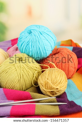 Multicolored clews with needles and bright scarf closeup - stock photo