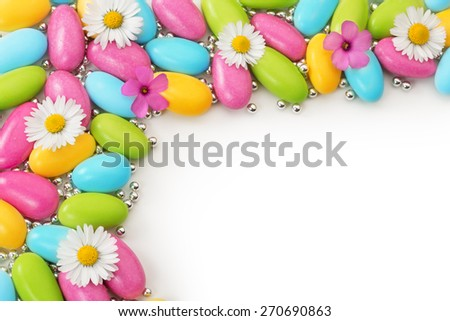 multicolored dragees and wildflowers on white background - stock photo