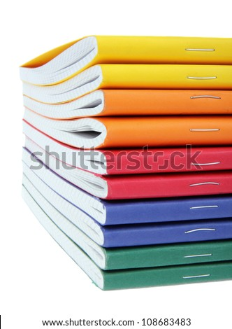 multicolored exercise books over the white background, close up. - stock photo