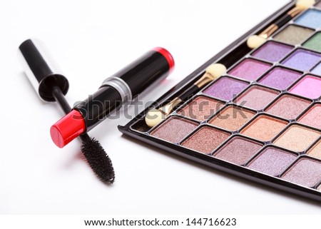 Multicolored eye shadows palette, red Lipstick and black mascara on white background, selective focus - stock photo