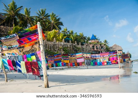 Multicolored fabric blowing in the light breeze next to clear water  - stock photo