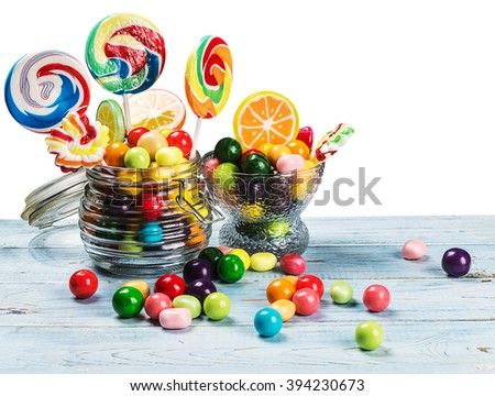 multicolored lollipops, candy and chewing gum in glass jar on a white background  - stock photo