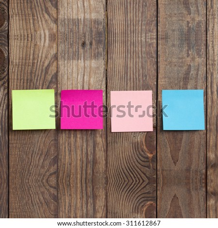 Multicolored paper stickers note on wooden background. Blank forms for workers notes - stock photo