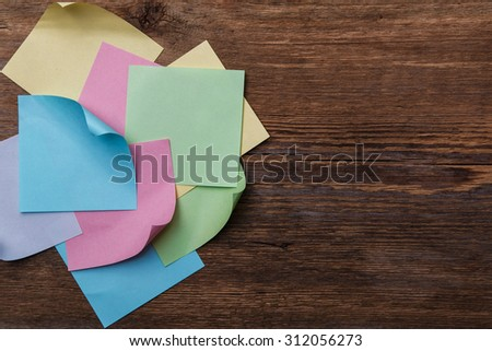Multicolored paper stickers on wooden table - stock photo