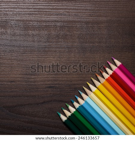 multicolored pencils on the brown wooden table in oder - stock photo