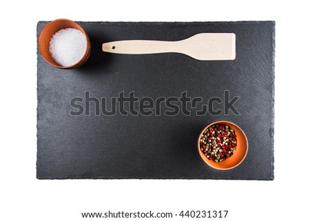multicolored peppers and salt in a clay cup on a slate board, wooden kitchen spatula, top view, isolated - stock photo