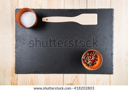 multicolored peppers peas and salt in a clay cup on a slate board, wooden kitchen spatula, top view - stock photo