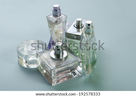 Multicolored perfumes in bottles of different shapes on a gray background - stock photo