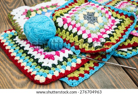 multicolored plaid squares of crocheted on a wooden background - stock photo