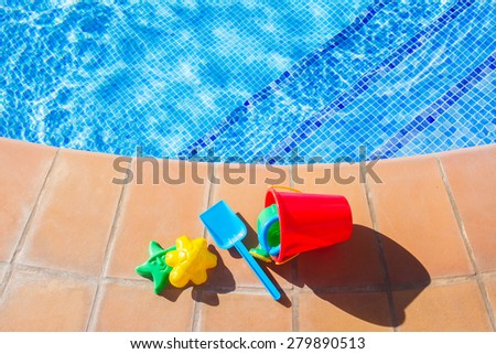 multicolored plastic beach toys pool  blue water - stock photo