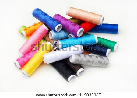 Multicolored sewing threads on white background - stock photo