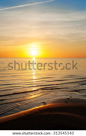 Multicolored summertime sunset on Baltic sea beach. Vertical outdoors image - stock photo