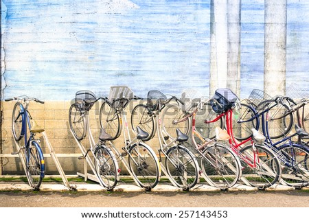 Multicolored vintage bicycles in metal rack in Tokyo city - Urban ecological transportation concept with retro bikes - Ryogoku residential district in the japanese world famous capital - Logos removed - stock photo
