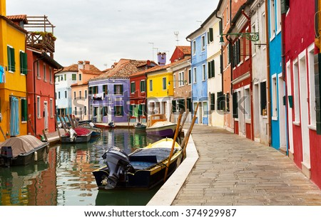 Multicolored walls of houses and motor boats on Burano island, Venice - stock photo