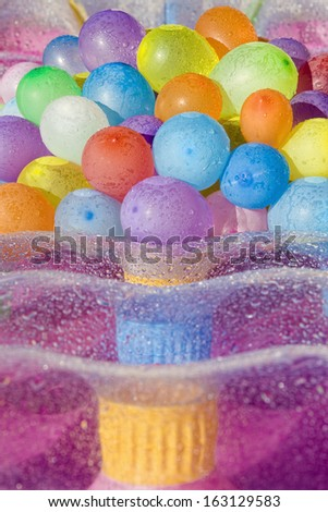 Multicolored water filled colored balloons laying on a moistened airbed - stock photo