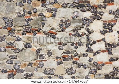 Multicoloured stone background of a building exterior facade with different sizes, colours and textures of stones. - stock photo