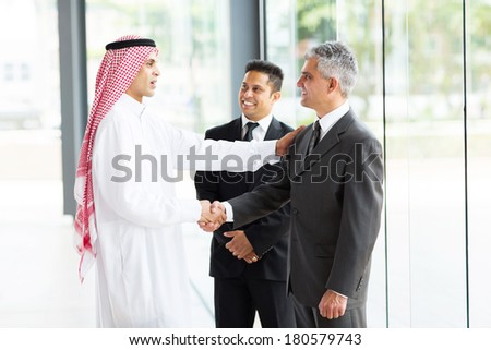 multicultural business partners handshaking in office - stock photo