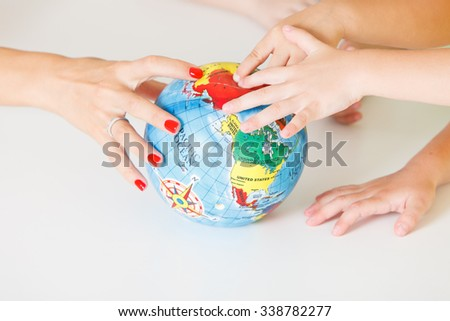Multicultural childrens hands on a globe - stock photo