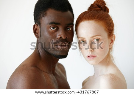Multicultural love and relationships concept: young nude redhead freckled Caucasian woman standing next to her shirtless African boyfriend, looking at the camera with serious face expression - stock photo