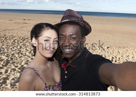 Multicultural young couple taking selfie smiling  in love  on beach having fun stock - stock photo