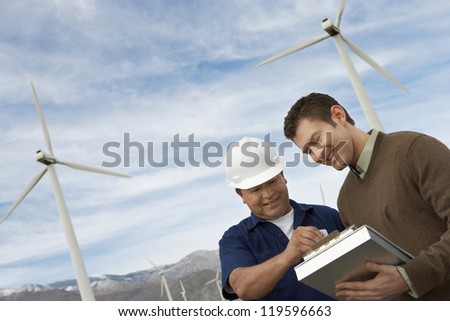 Multiethnic architects working together at wind farms - stock photo