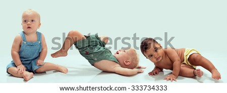 Multiethnic babies dancing on light background - stock photo