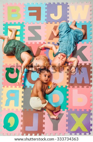 Multiethnic babies lying around on  Alphabet puzzle background - stock photo