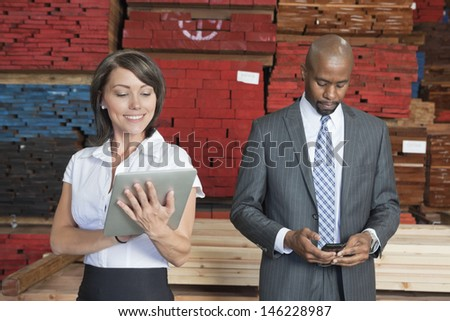 Multiethnic business colleagues using tablet PC and cell phone with stacked wooden planks in background - stock photo