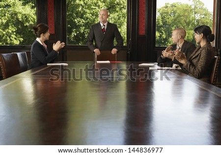 Multiethnic business people applauding to male leader for good presentation in boardroom - stock photo