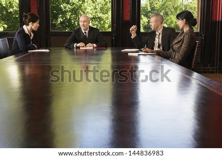 Multiethnic business people having discussion at conference table - stock photo