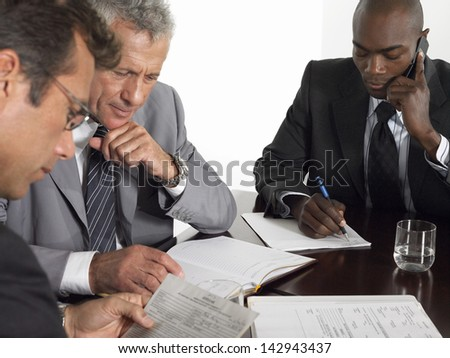 Multiethnic businessmen with paperwork at conference table - stock photo