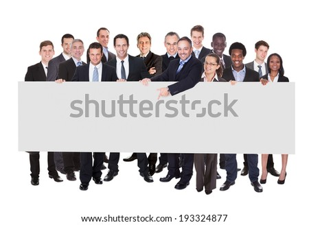 Multiethnic businesspeople holding blank billboard against white background - stock photo
