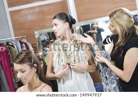 Multiethnic fashion model and female stylist in dressing room - stock photo
